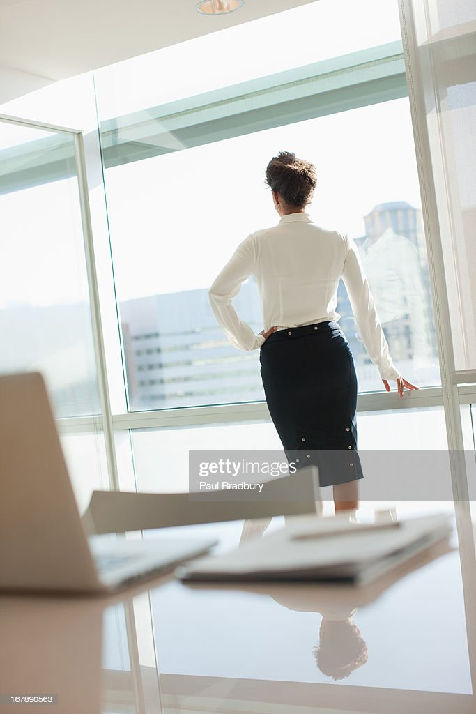 Businesswoman looking out office window : Stock Photo