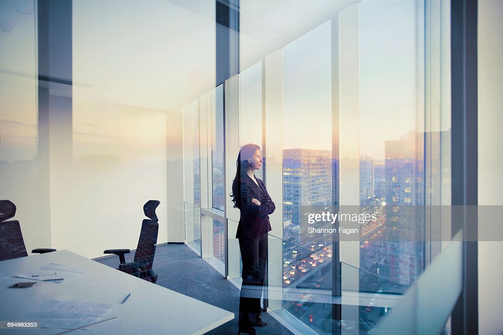 Businesswoman looking out window in meeting room : ストックフォト