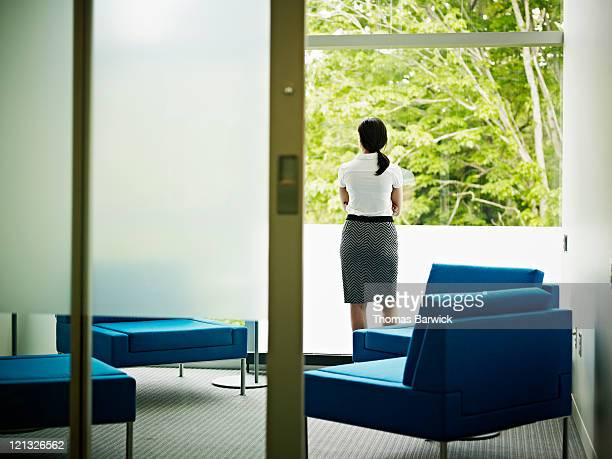 Businesswoman looking out window of office