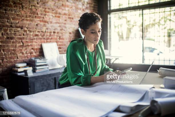 businesswoman looking over architecture blueprints in office - entrepreneur stock pictures, royalty-free photos & images