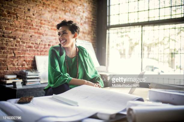 businesswoman looking over architecture blueprints in office - kleinunternehmen stock-fotos und bilder