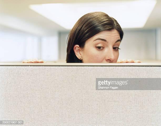 businesswoman looking over partition, close-up - entrometido fotografías e imágenes de stock