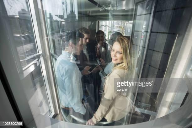 ガラス張りのエレベーターの肩越しに見ている実業家 - looking over shoulder ストックフォトと画像