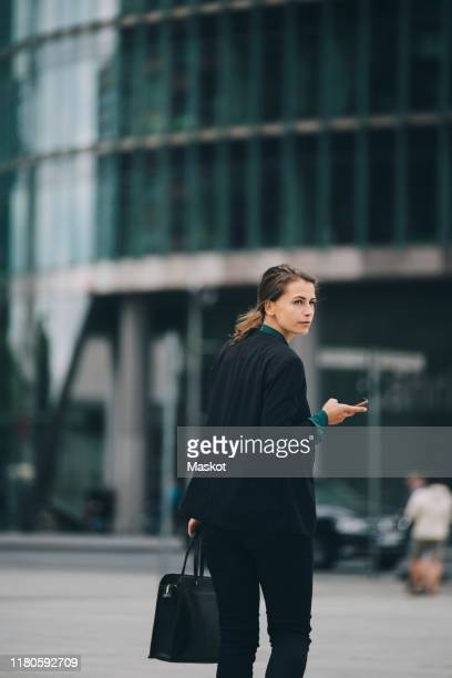 businesswoman looking over shoulder while walking on street in city - 肩ごしに見る ストックフォトと画像