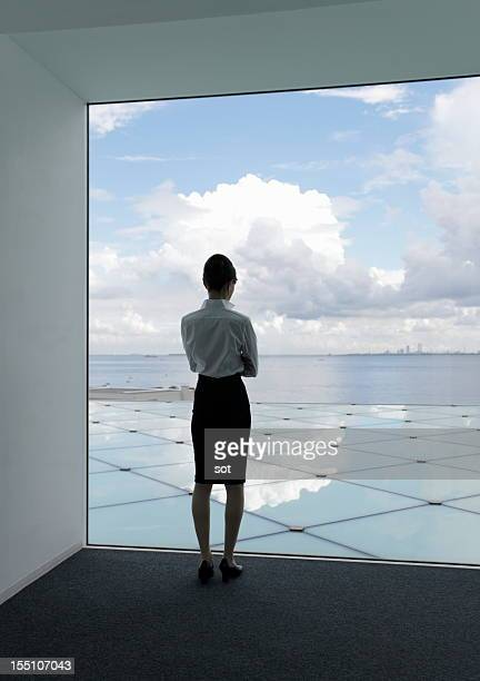 Businesswoman looking skyscape from the window