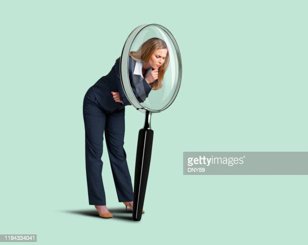 businesswoman looking through large magnifying glass - magnifying glass stock pictures, royalty-free photos & images