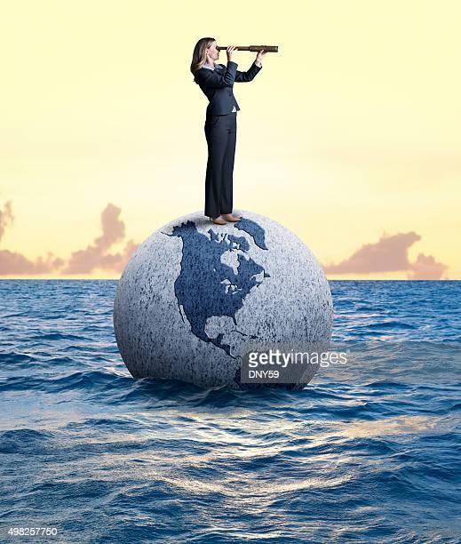 Businesswoman Looking Through Spyglass Standing On A Globe