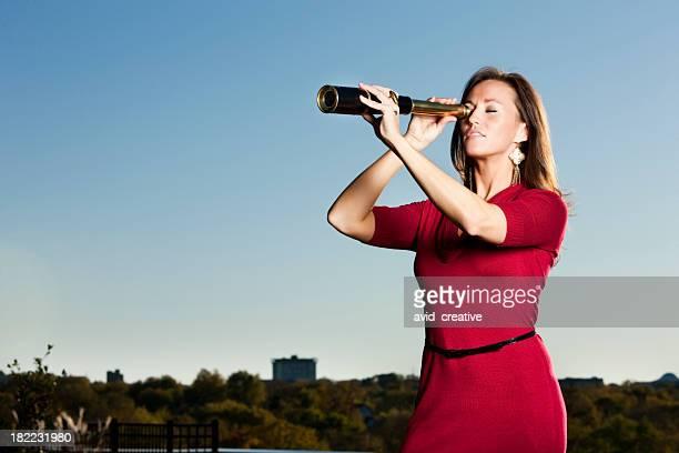 Mujer de negocios mirando a través del telescopio
