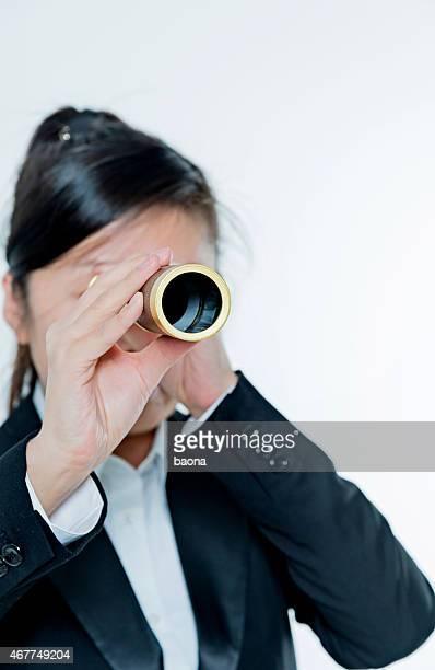 Femme d'affaires regardant à travers un télescope