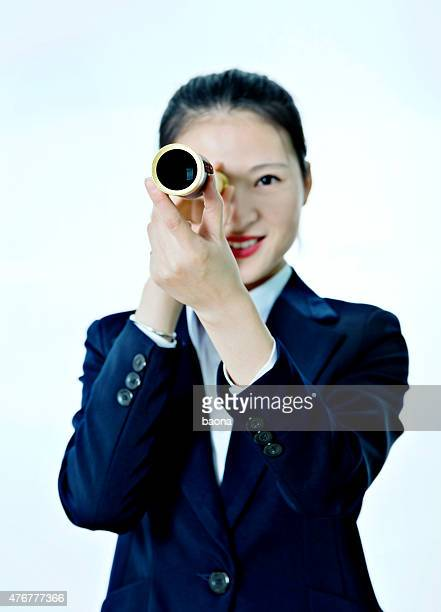 Femme d'affaires regardant à travers un télescope