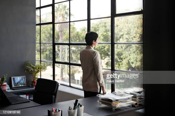 businesswoman looking through window at workplace - cream coloured blazer stock pictures, royalty-free photos & images