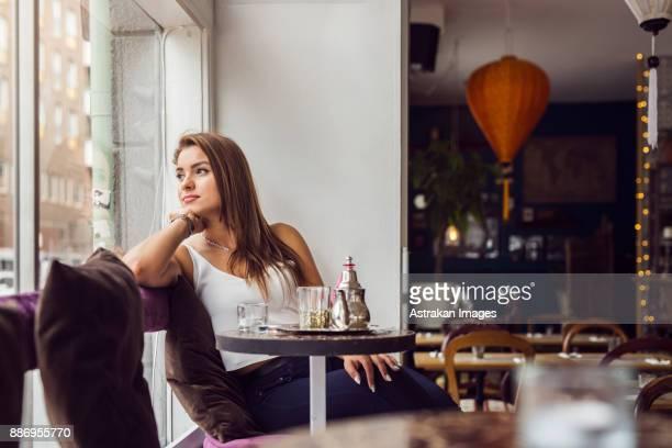 Businesswoman looking through window in restaurant