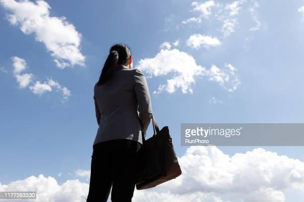 businesswoman looking up against sky - 見上げる ストックフォトと画像