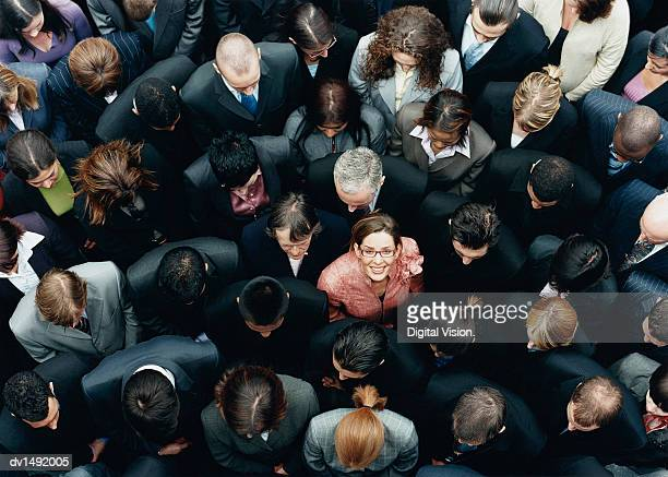 businesswoman looking up at camera and standing outdoors surrounded by a large group of business people - individualität stock-fotos und bilder