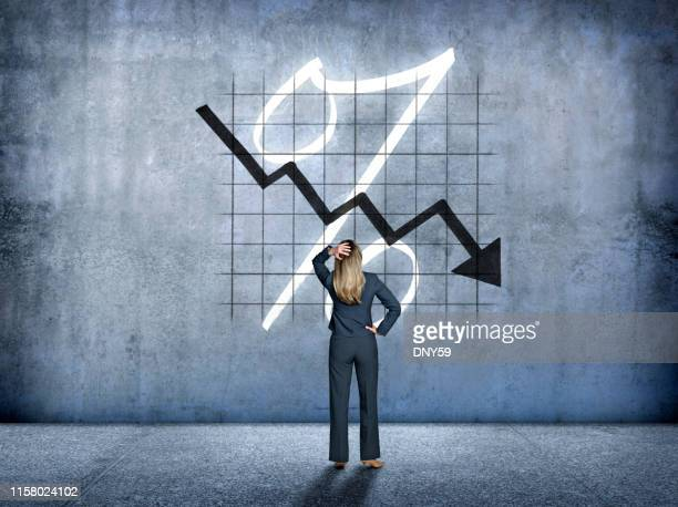 businesswoman looking up at falling interest rates - percentage sign stock pictures, royalty-free photos & images
