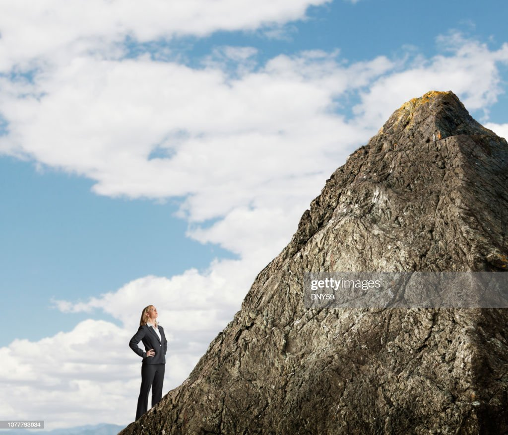 Businesswoman Looking Up At Mountain Peak : Stock Photo