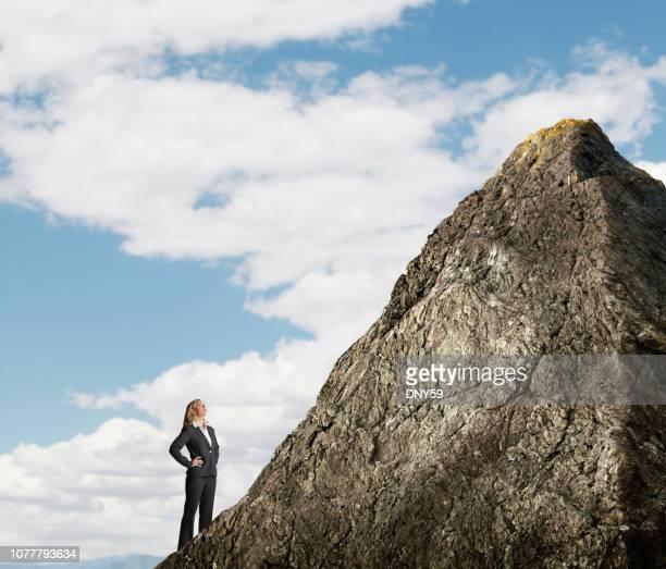 Femme d'affaires à la recherche de haut au sommet de la montagne