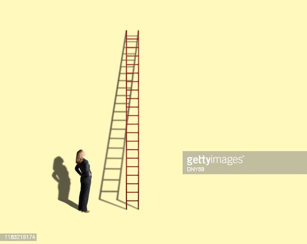 businesswoman looking up at tall ladder on yellow background - ladder stock pictures, royalty-free photos & images