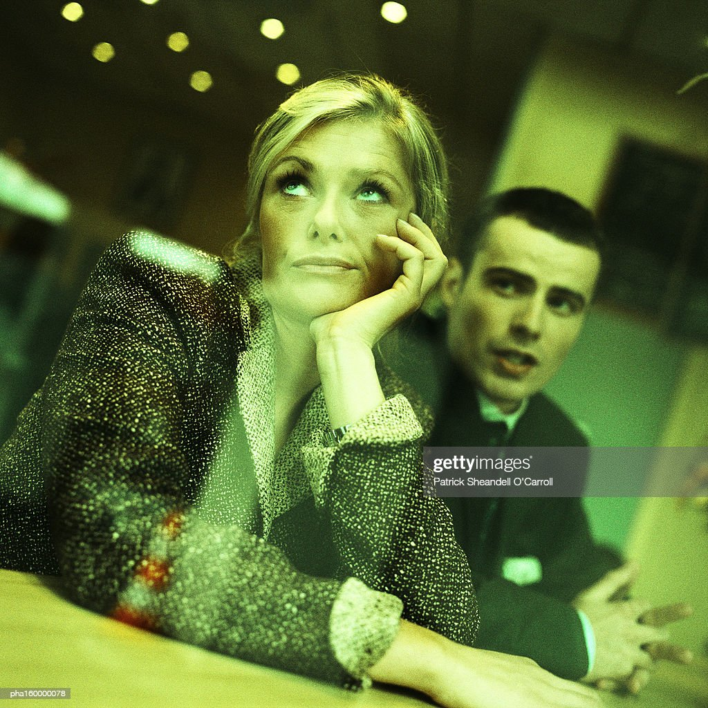 Businesswoman looking up, man sitting behind her, view through window from outside, portrait. : Stockfoto