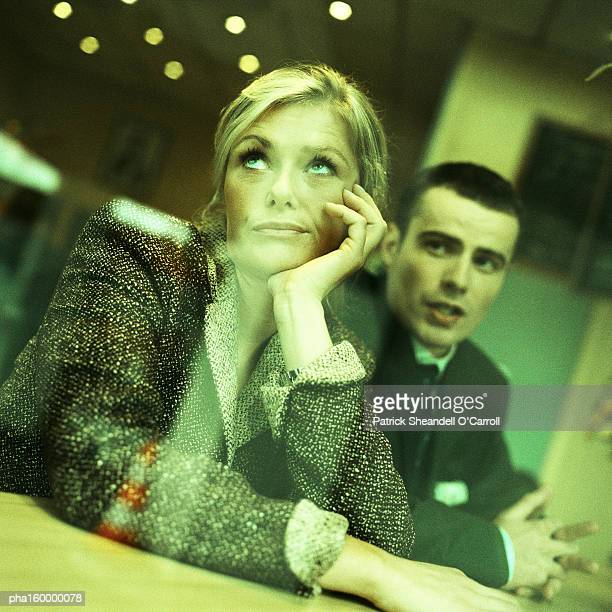 Businesswoman looking up, man sitting behind her, view through window from outside, portrait.