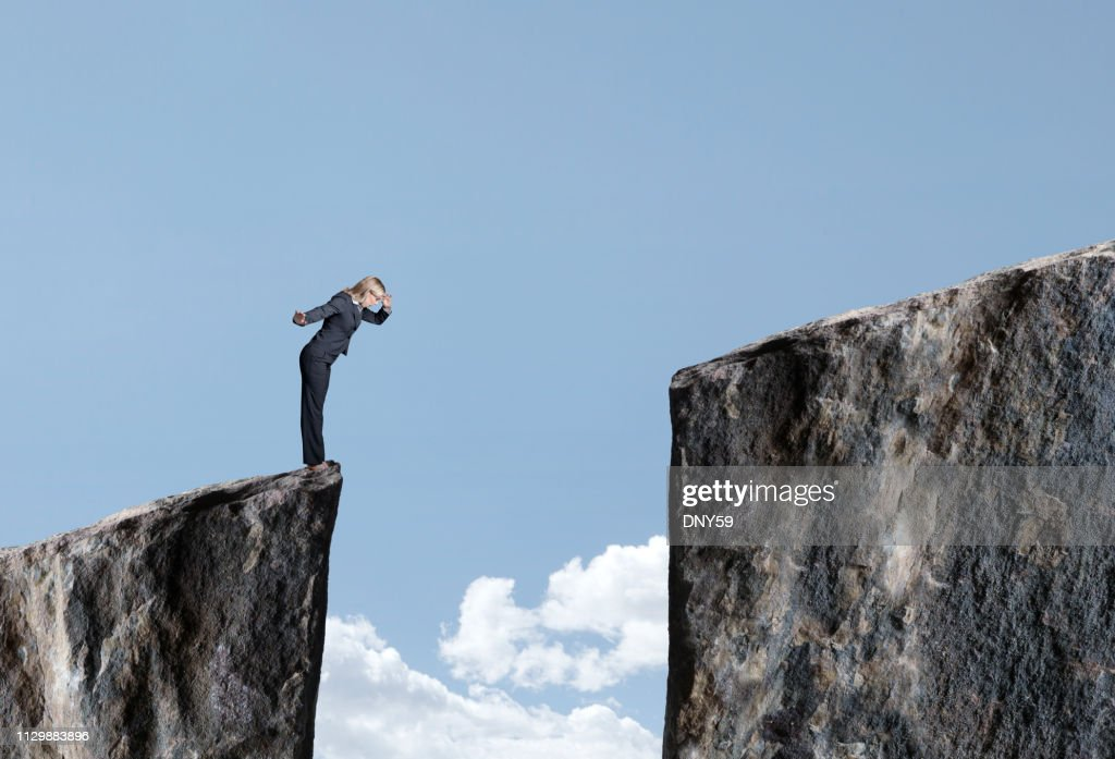 Businesswoman Looks Down At Large Gap Between Two Cliffs : Stock Photo