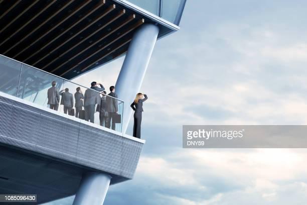 empresaria se ve en la distancia mientras que los empresarios ven en la dirección opuesta - riesgo fotografías e imágenes de stock