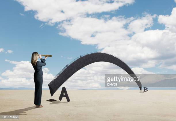 businesswoman looks through spyglass for shortest distance between two points - letra b imagens e fotografias de stock
