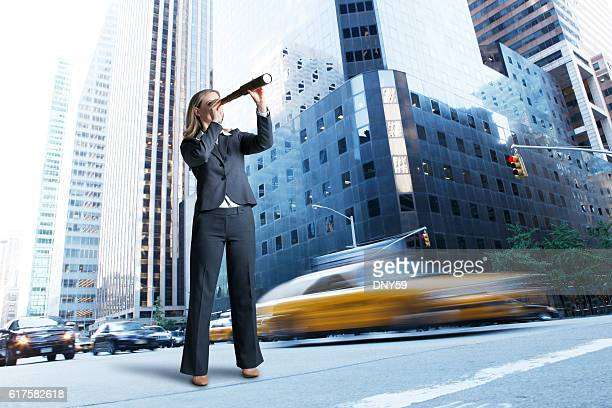 Businesswoman Looks Through Spyglass While Standing In Busy Urban Street