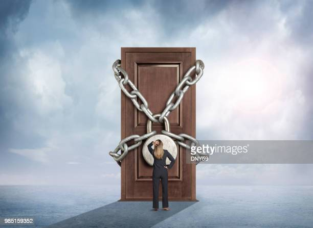 businesswoman looks up at a door that is padlocked - social inequality stock pictures, royalty-free photos & images