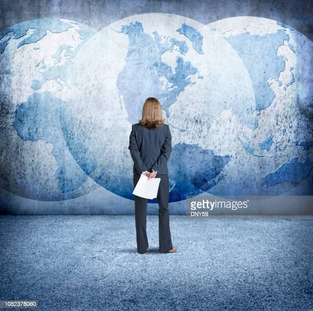 Businesswoman Looks Up At Three Interlocking Globes On Wall