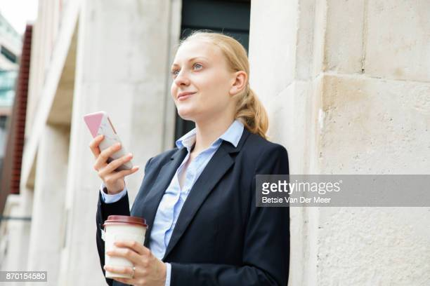 Businesswoman looks up from smart phone, holding take away coffee.