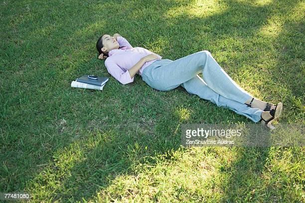 Businesswoman lying in grass, eyes closed