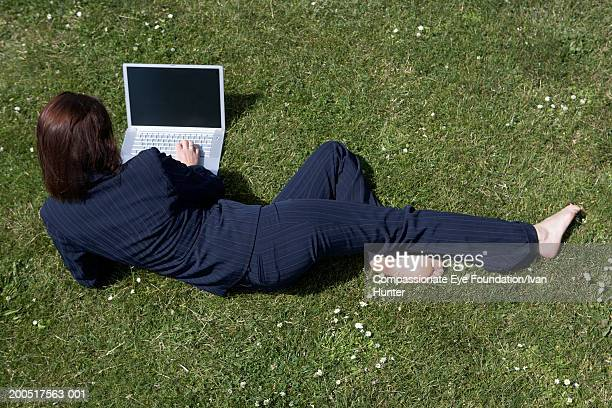 Businesswoman lying on grass, using laptop, elevated view