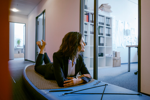 Businesswoman lying on paddle board, daydreaming in office - gettyimageskorea