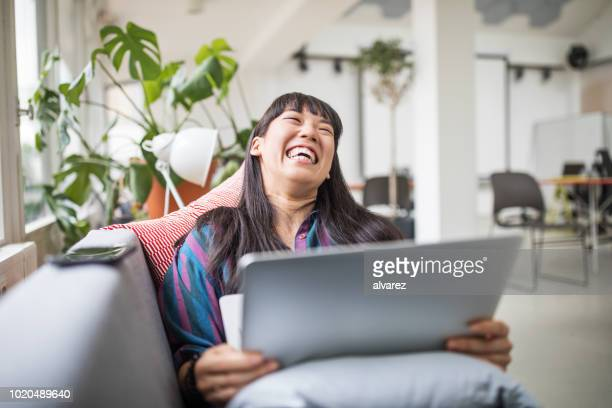 businesswoman lying on sofa with laptop in modern office lounge - cool attitude stock pictures, royalty-free photos & images