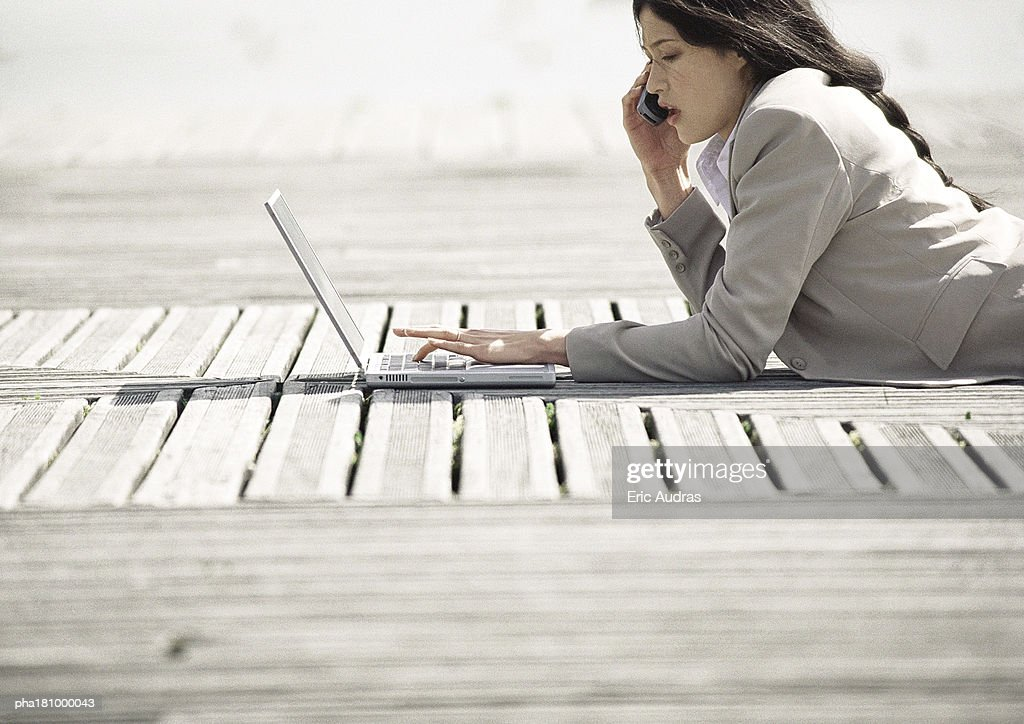Businesswoman lying on stomach with laptop computer, outdoors : Stockfoto