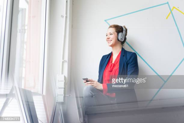 Businesswoman making a call, wearing headphones