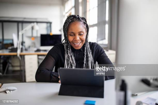 businesswoman making a video call with digital tablet - african american ethnicity stock pictures, royalty-free photos & images