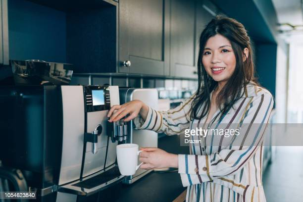 businesswoman making coffee during coffee break - coffee maker stock pictures, royalty-free photos & images