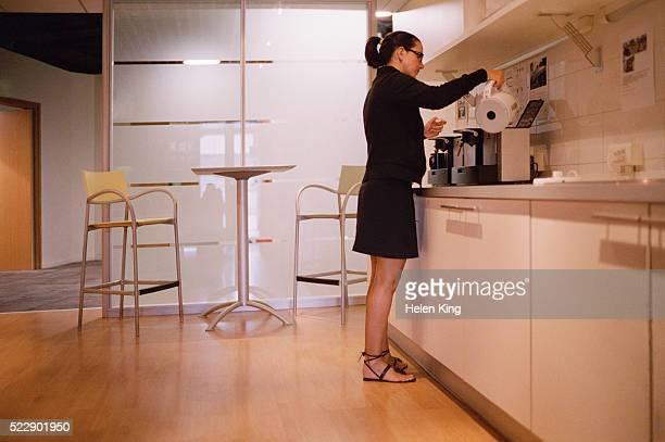 Businesswoman Making Coffee in Breakroom