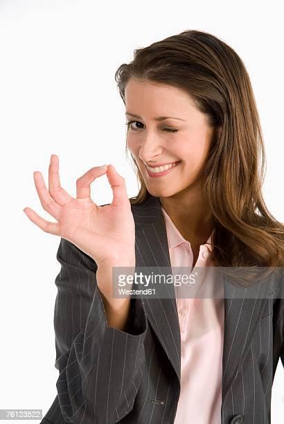 Businesswoman making ok sign, winking, portrait, close-up