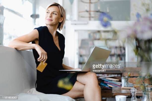 businesswoman making online payment, sitting in coffee shop, using laptop and credit card - credit card purchase stock pictures, royalty-free photos & images