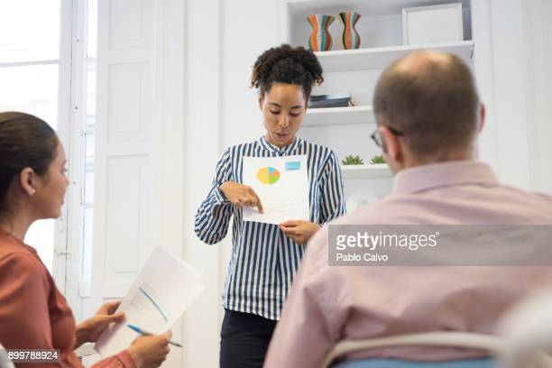Businesswoman making pie chart presentation at boardroom table