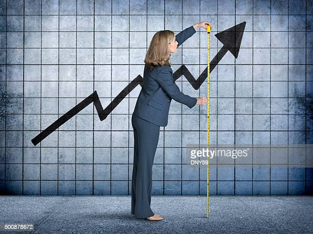 businesswoman measures growth with tape measure - measuring stock pictures, royalty-free photos & images