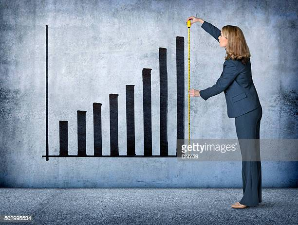 businesswoman measures growth with tape measure - business strategy stock photos and pictures