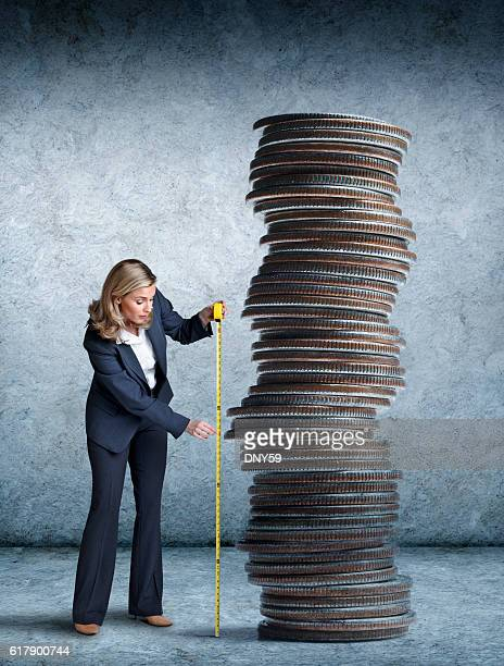 Businesswoman Measuring A Stack Of Coins With Tape Measure