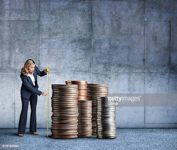 Businesswoman Measuring A Stacks Of Coins With Tape Measure