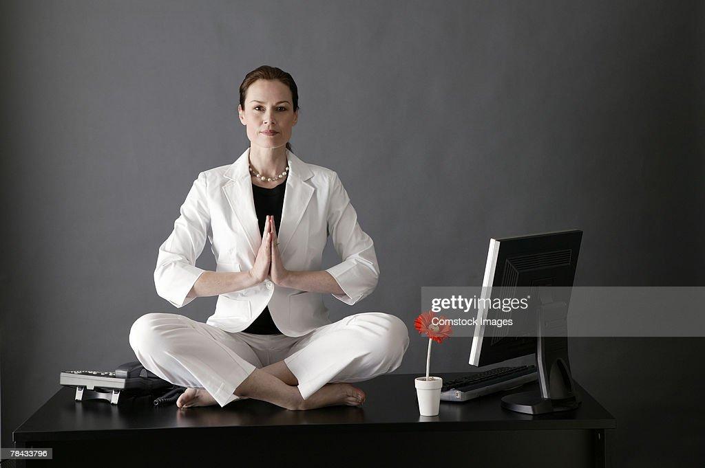 Businesswoman meditating on desk : Stockfoto