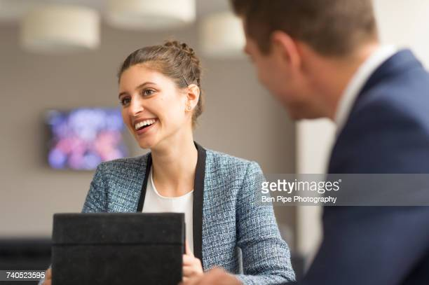 Businesswoman meeting male colleague in boardroom