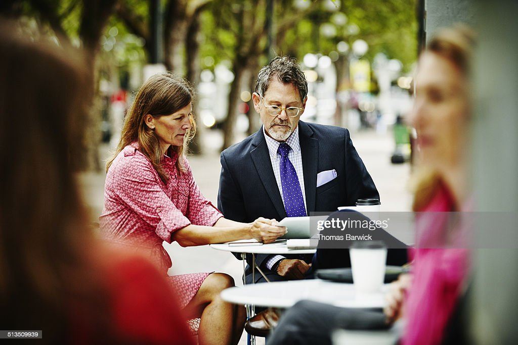 Businesswoman meeting with client at urban cafe : Stock Photo